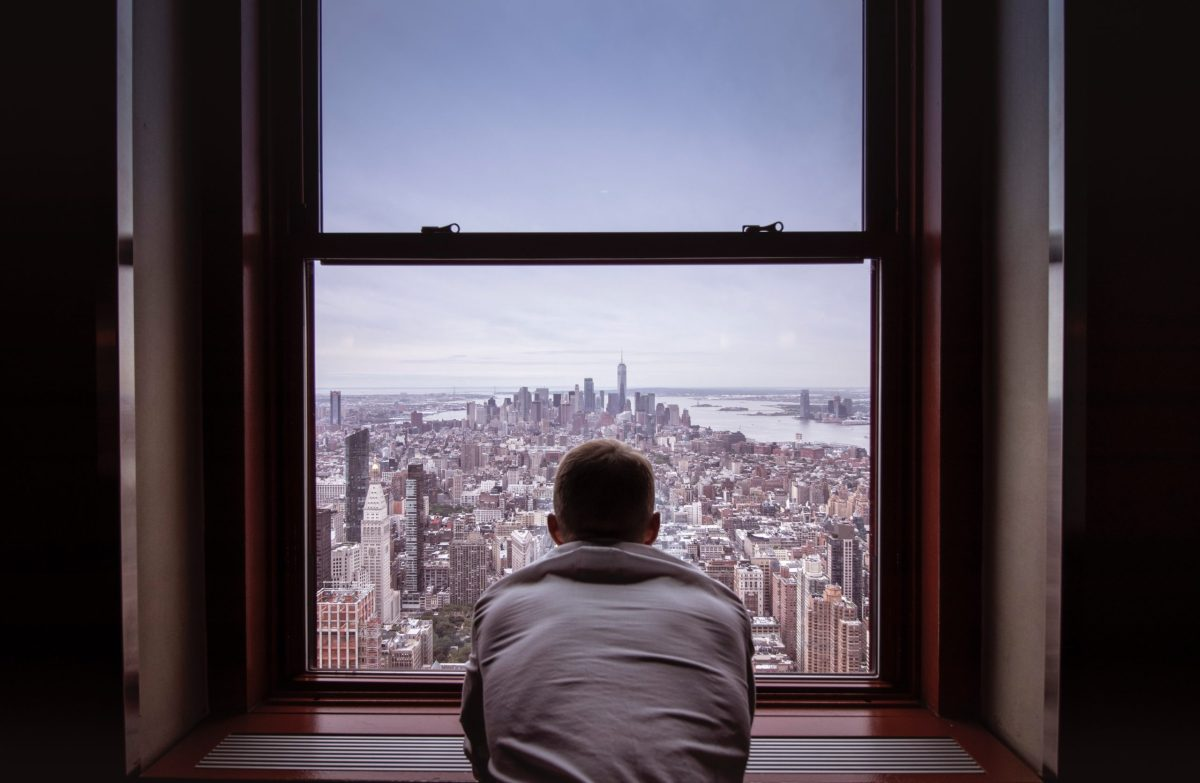 Man looking out at NYC from inside